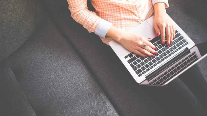 Person in Orange Checkerd Shirt Sitting on Sofa Typing on Laptop