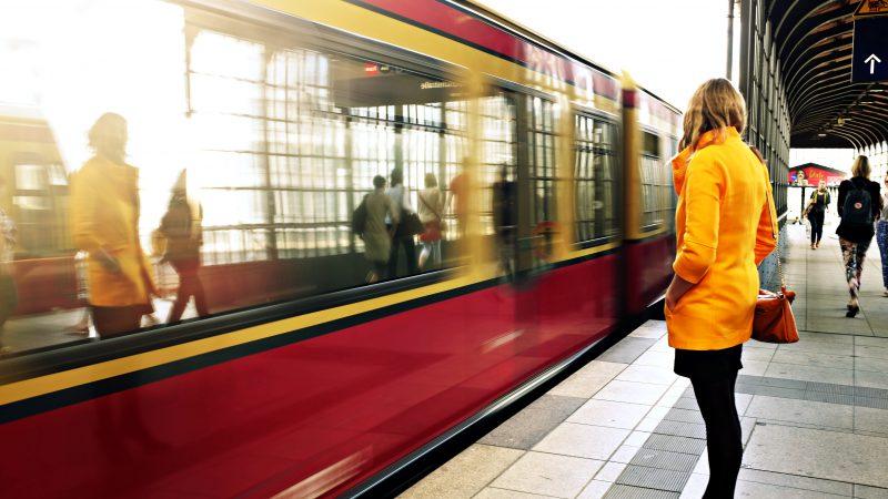 Woman in Orange Coat Waiting for Train