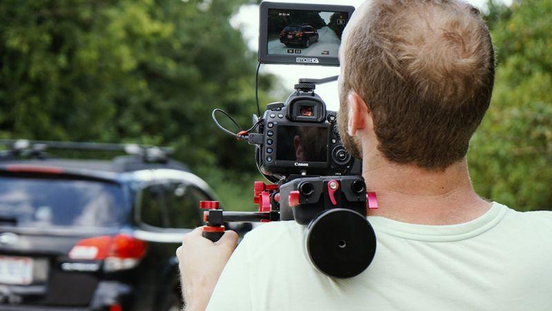 Man with TV Camera Shooting Car Driving Down Road